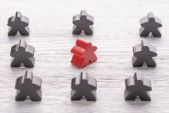 Uniqueness, individuality and difference. Red wooden figure in a crowd of different color stock images