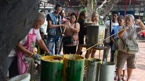 Unire della gente tailandese che fonde offerta fusa della candela al tempio nel festival prestato tradizionale della candela per  video d archivio