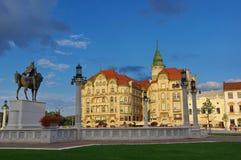 Unirii-Quadrat in Oradea - schwarzer Eagle Palace und Statue von Mihai Viteazul Stockbild
