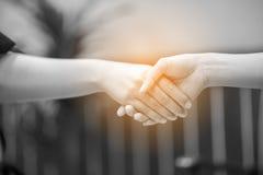 Unisca le mani di due genti Ed il saluto degli amici Commu fotografie stock