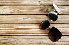 2 unisex солнечного очк на деревянном взгляд сверху предпосылки Стоковая Фотография RF