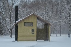 Unisex outhouse in a snowy campground stock photos