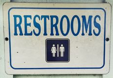 Unisex Restroom Metal Sign. Outdoors on a wooden wall. Men`s and Women`s Restroom sign royalty free stock images