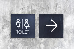 Unisex restroom or Toilet and arrow sign on  concrete wall style Stock Photography