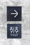 Unisex restroom or Toilet and arrow sign on  concrete wall style Royalty Free Stock Images