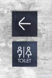 Unisex restroom or Toilet and arrow sign on  concrete wall style Royalty Free Stock Image