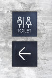 Unisex restroom or Toilet and arrow sign on  concrete wall style Royalty Free Stock Photos