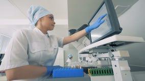 Unità del laboratorio con attrezzature di funzionamento e parecchi esperti femminili che lavorano in  video d archivio