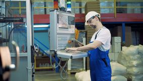 Unità di stoccaggio con un lavoratore che dirige una console di controllo stock footage