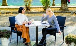 Unità ed amicizia femminile Sela fidi di Gli amici di ragazze bevono il caffè e godono della conversazione Fine amichevole di ver immagine stock