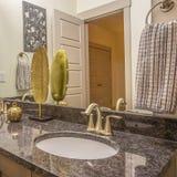 Unité élégante de vanité de cadre carré à l'intérieur d'une salle de bains avec les armoires en bois et le double évier images libres de droits