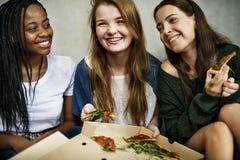 Unité d'amitié d'amie mangeant la culture Co de la jeunesse de pizza Photos libres de droits
