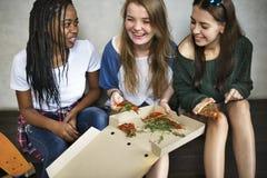 Unité d'amitié d'amie mangeant la culture Co de la jeunesse de pizza Images stock