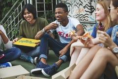 Unité d'amitié de personnes mangeant la culture Concep de la jeunesse de pizza Photo stock