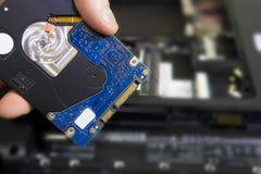 Unité de disque dur d'ordinateur portable dans la main du spécialiste en réparation d'ordinateur sur le fond du carnet démonté Photo stock