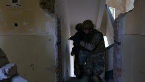 Unité de soldats entrant dans le bâtiment ruiné vérifiant leur objectif militaire banque de vidéos