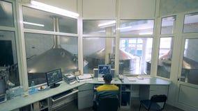 Unité de surveillance à une usine de distillerie avec un homme s'asseyant dans elle et observant le processus banque de vidéos