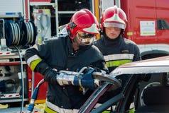 Unités de secours du feu et de délivrance à l'accident de voiture Photo libre de droits