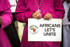 Unite Africa. Bishop holding a sign that reads Africas Let`s Unite stock image