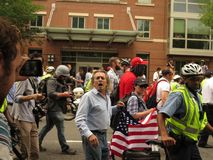 Racist man yells at counterprotesters at alt-right protest. UNITE THE RIGHT 2018, DC, AUG. 12: A man holding an American flag yells `stop the hate!` at royalty free stock photography