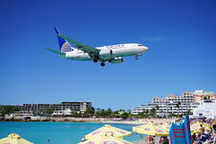 A United Airlines Boeing 737 lands over Maho Beach in St Martin. SAINT MARTIN, DUTCH ANTILLES --30 NOVEMBER 2014-- The beach at Maho Bay is one of the world's Stock Photo