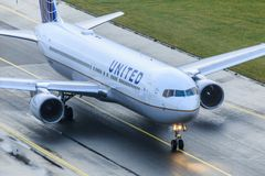 United Airlines Boeing 767 taxiing. Boeing 767-300 of United Airlines taxiing on wet taxiway royalty free stock image