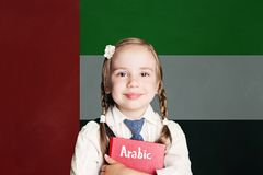 United Arab Emirates concept with happy child girl student with red book against the United Arab Emirates flag background. stock photo