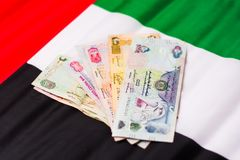 United Arab Emirates currency on top of flag Royalty Free Stock Photography