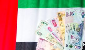 United Arab Emirates currency on top of flag Royalty Free Stock Photos