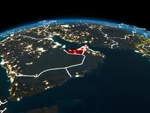United Arab Emirates on Earth at night. Space orbit view of United Arab Emirates highlighted in red on planet Earth at night with visible country borders and Stock Photos