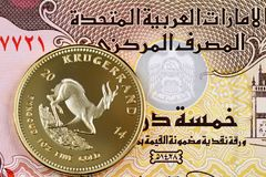 Five UAE dirham bank note with a golden Krugerrand coin stock photography