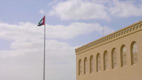United Arab Emirates flag flying against clean and tranquil sky. Corner of beige arabian building at blue sky with white clouds stock footage