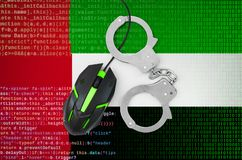 United Arab Emirates flag and handcuffed computer mouse. Combating computer crime, hackers and piracy. United Arab Emirates flag and handcuffed modern backlit stock photography