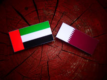United Arab Emirates flag with Qatari flag on a tree stump isolated. United Arab Emirates flag with Qatari flag on a tree stump Stock Photo