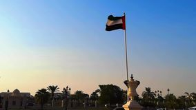 The United arab emirates flag waving in Sharjah city at sunset.  stock footage