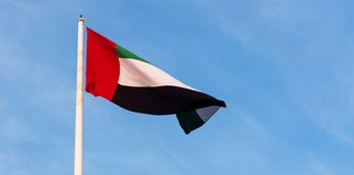 United Arab Emirates flag against blue sky. United Arab Emirates flag winding in the wind against blue sky royalty free stock images