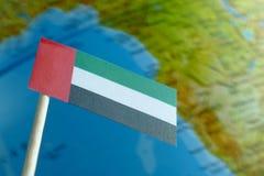 United Arab Emirates señalan por medio de una bandera con un mapa del globo como fondo Imagen de archivo