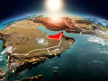 United Arab Emirates in sunrise from orbit. Sunrise above United Arab Emirates highlighted in red on model of planet Earth in space with visible country borders Royalty Free Stock Photography