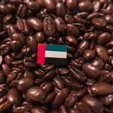 A United Arab Emirates, UAE flag placed over roasted coffee beans royalty free stock photography