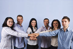United business people with hands together. United big group of six business people standing with their hands together in front of blue background,,concept of Stock Photo