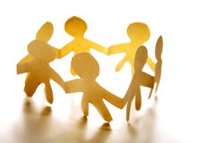 United Children. A metaphorical image of a paper cutout of children making a circle holding hands, depicting unity Stock Image