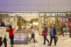 United Colors of Benetton. People passing by United Colors of Benetton shop located in a mall Royalty Free Stock Photo