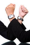 United in difference. Two hand of different skin tones using watches placed against each other Stock Photos