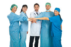 United doctors team. Standing with their hands on top each other isolated on white background