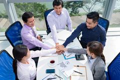 United efforts. Businesspeople stack their hands as the symbol of united efforts Stock Photo