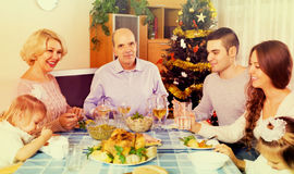 United family at festive table. Happy united family at festive table near Christmas tree Stock Photography