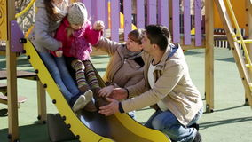 United family of four spending time together. Happy parents playing with little daughters at slide of playground stock footage