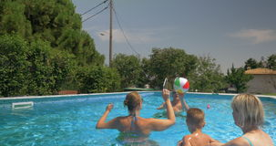 United Family Playing Inflatable Ball in Home Pool stock video footage