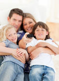 United family watching television sitting on sofa. At home Royalty Free Stock Photography