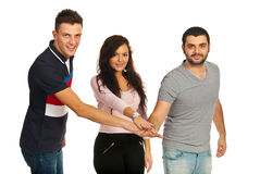 United friends. Standing with hands on top each other isolated on white background Stock Photo